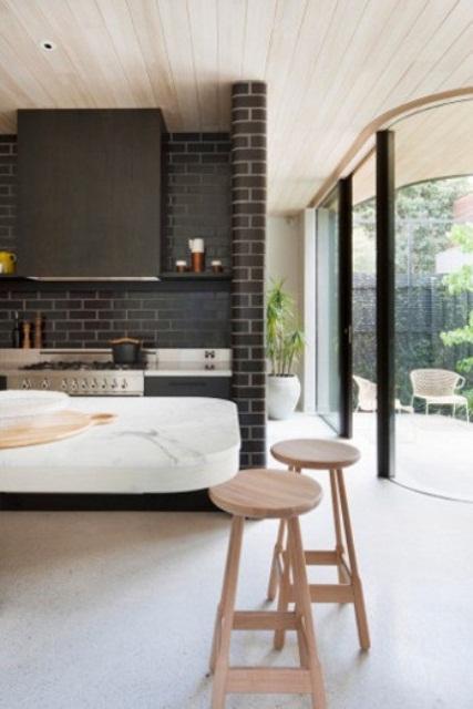 mattoni scuri evidenziati con stucco bianco e legno macchiato scuro compongono una cucina moderna audace e scura
