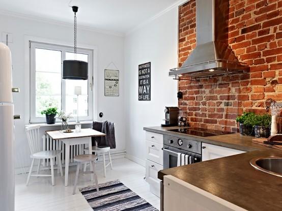 una cucina completamente bianca con un backsplash del fornello in mattoni rossi che aggiunge interesse, colore e persino carattere allo spazio