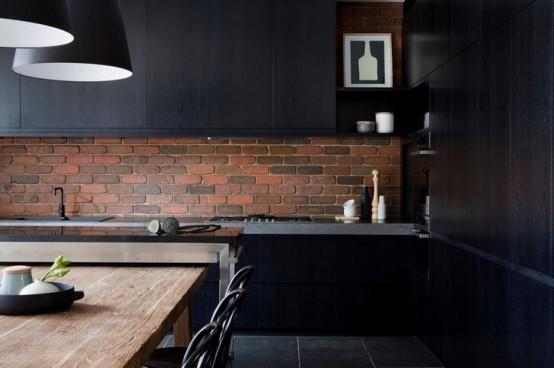 una cucina nera lunatica con un backsplash in mattoni rossi che ravviva lo spazio e lo rende più audace e più fresco