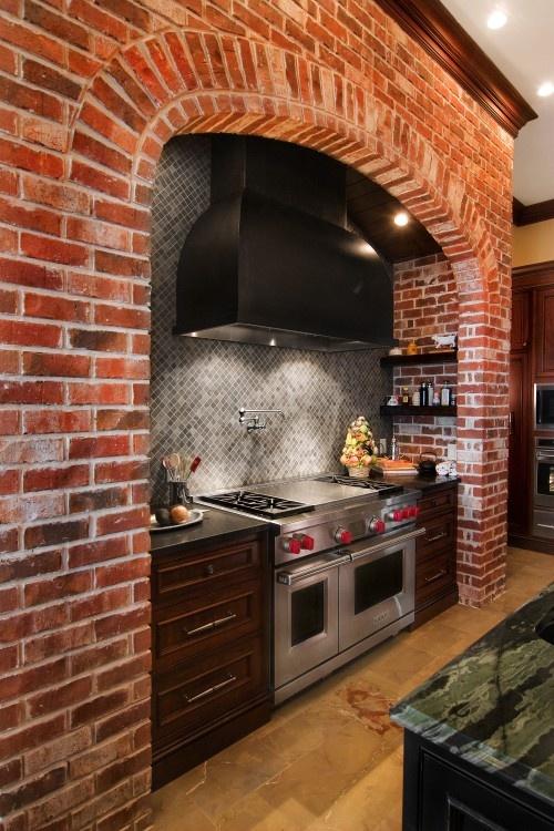 un backsplash del fornello in mattoni rossi con ripiani e piastrelle grigie compone lo spazio chic e materico