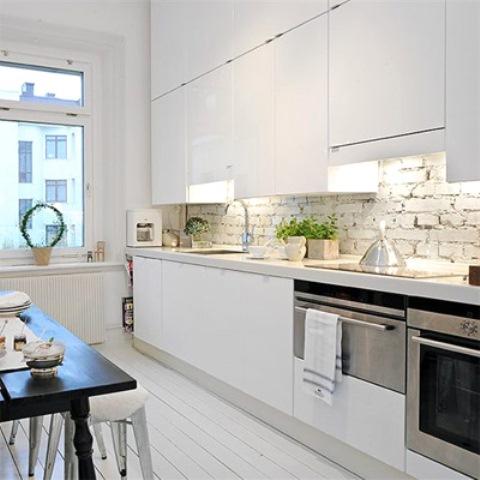 eleganti armadi bianchi sono completati da un backsplash in mattoni bianchi e un pavimento in legno bianco che aggiungono consistenza allo spazio