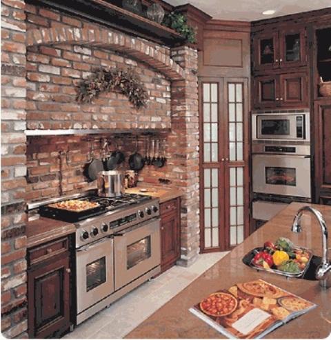 un backsplash e un muro del fornello in mattoni rossi più mobili in legno riccamente colorati per un'elegante cucina rustica
