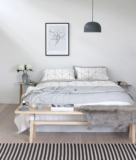 una camera da letto nordica casual in bianco sporco, con una panca in legno, un comodo letto e una lampada a sospensione per un look moderno