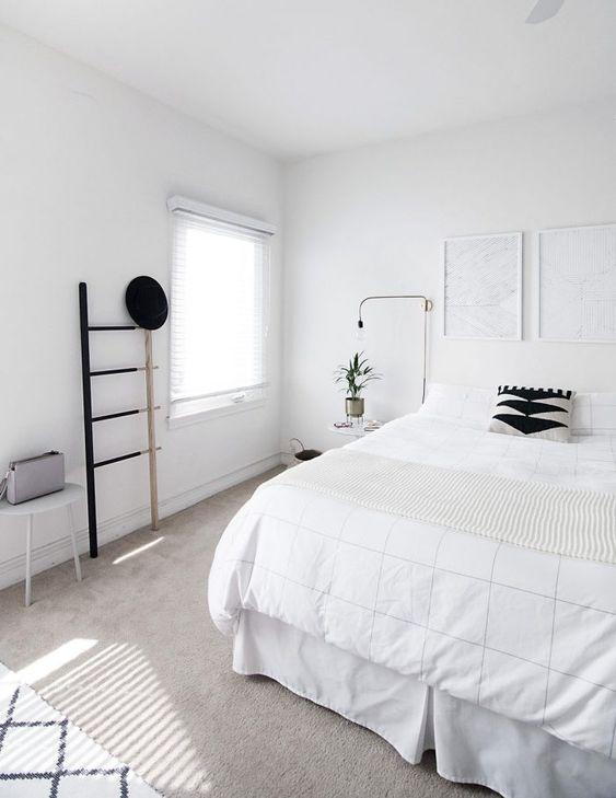 una camera da letto nordica pulita con un letto bianco, opere d'arte, una scala, lampade e uno sgabello - blakc per il dramma