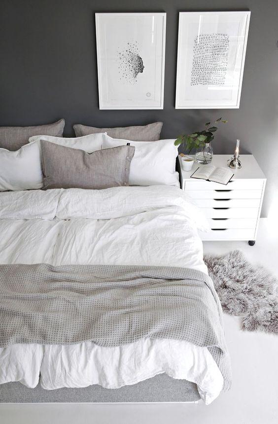 un'accogliente camera da letto scandinava con una parete nera, un letto con biancheria grigia, un comodino bianco e opere d'arte