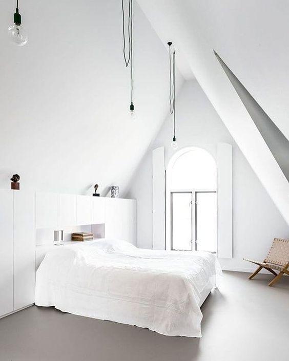 una camera da letto nordica pulita con una finestra ad arco, lampadine sospese, contenitori, un letto e una sedia di vimini