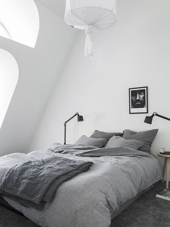 un'accogliente camera da letto nordica mansardata con finestre ad arco, un letto, lampade da tavolo, un'opera d'arte e una lampada a sospensione