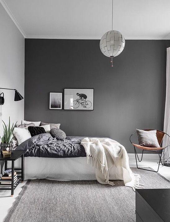 una camera da letto scandinava contemporanea con una parete scura, biancheria da letto monocromatica, lampade e luci e un tappeto grigio
