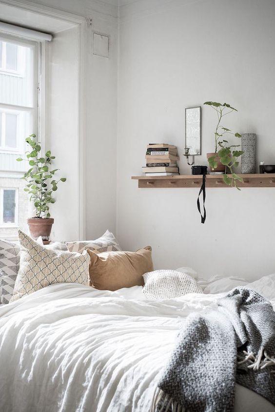 un'incantevole camera da letto con un letto, una mensola aperta, un po 'di verde in vasi e biancheria da letto neutra