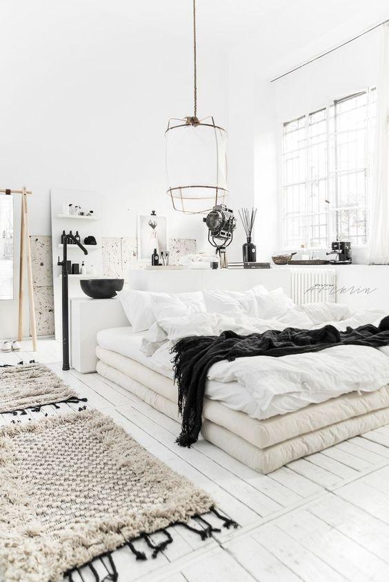 una camera da letto scandinava con un letto di materassi, lampade a sospensione, tappeti intrecciati e un bagno qui dentro