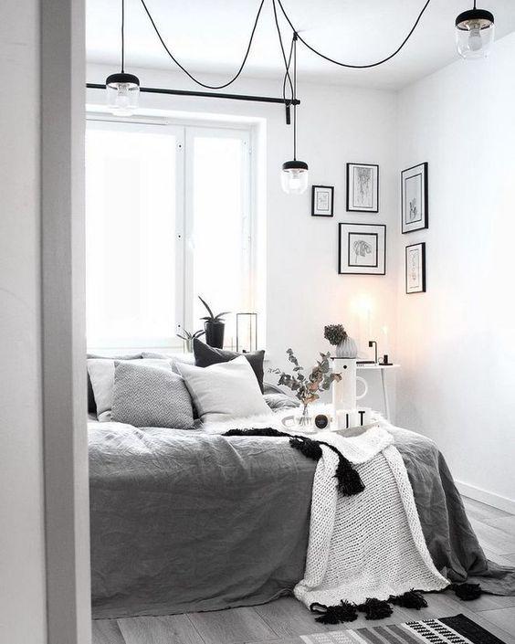 una camera da letto Scandi monocromatica con un letto con lenzuola grigie e bianche, alcune lampade, luci e una galleria a parete