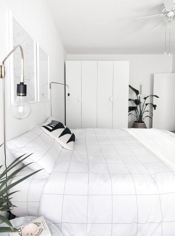 un minimalista incontra una camera da letto nordica con eleganti contenitori, un letto, alcune lampadine e opere d'arte