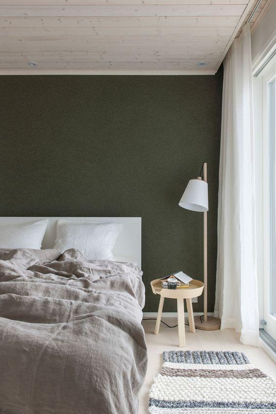 una semplice camera da letto nordica con un muro nero, un letto bianco, mobili in legno e un tappeto intrecciato