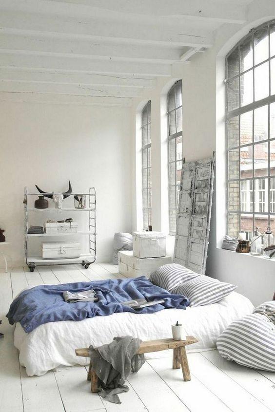 una zona notte scandinava con finestre di grandi dimensioni, uno scaffale su rotelle, un letto comodo e alcuni mobili in legno
