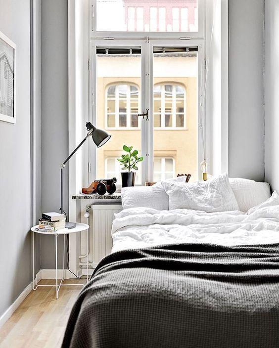 una piccola camera da letto nordica con un letto, un comodino con una lampada, piante in vaso e pareti grigie