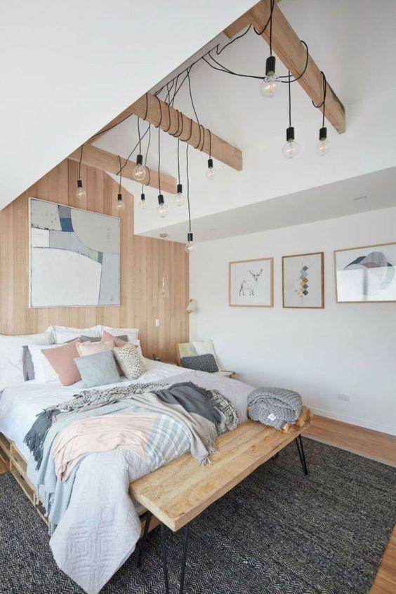una camera da letto scandinava con un letto e una panca in legno, alcune lampadine pendenti e tocchi pastello