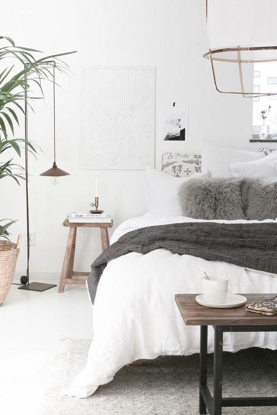 una camera da letto scandinava con un letto bianco, alcuni mobili in legno, lampade a sospensione, opere d'arte e piante in vaso