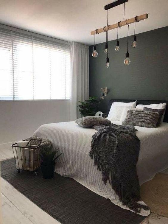 un'elegante camera da letto scandinava con un muro nero, un letto nero, un pezzo sospeso con lampadine e un tappeto