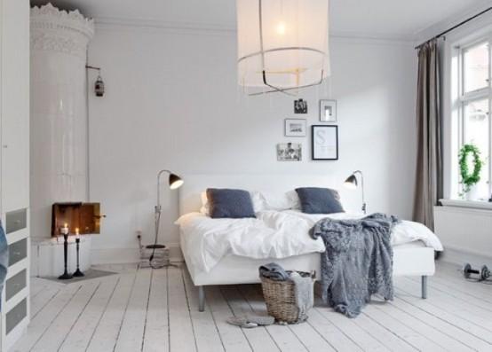 una tranquilla camera da letto scandinava bianca con una stufa tradizionale, un letto imbottito, una lampada a sospensione