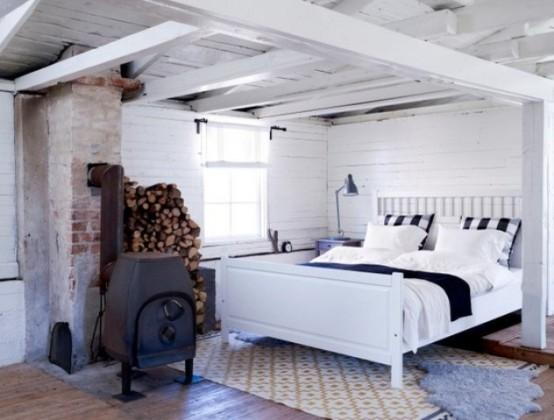 una camera da letto nordica di ispirazione vintage in bianco, con assi bianche, un focolare in metallo e un comodo letto più tappeti