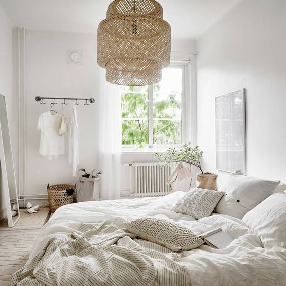 una camera da letto nordica ariosa con un paralume in vimini, cuscini all'uncinetto, mobili neutri e molta luce