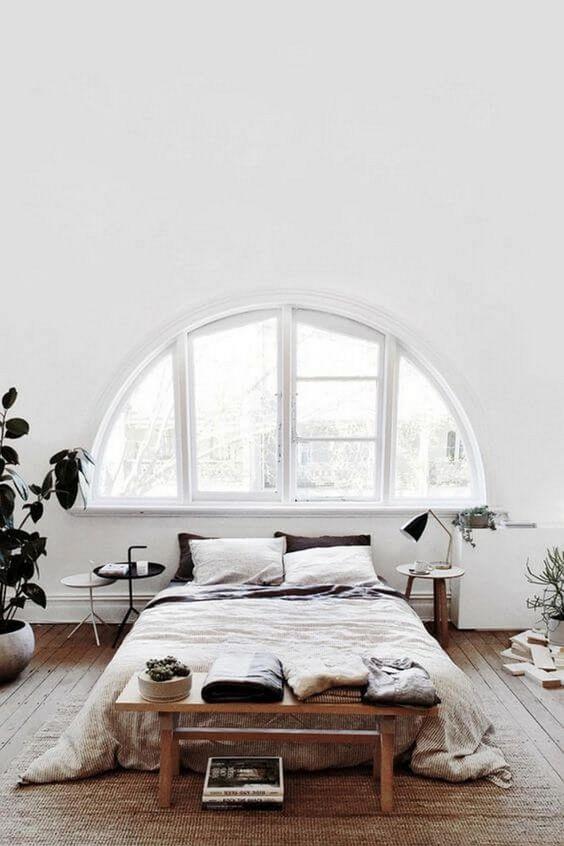 una camera da letto nordica bianca ariosa con una finestra ad arco, un letto, alcuni mobili in legno e piante in vaso