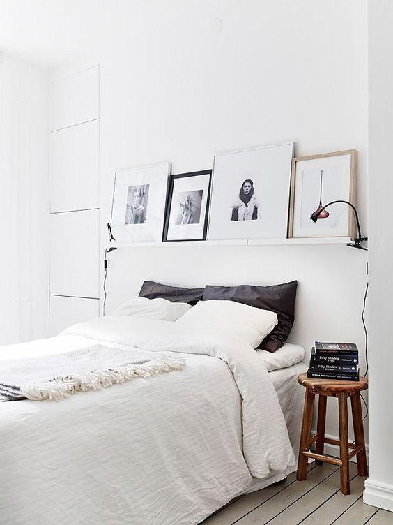 una camera da letto nordica bianca con una sporgenza con opere d'arte, un letto comodo, sgabelli in legno come comodini e lampade