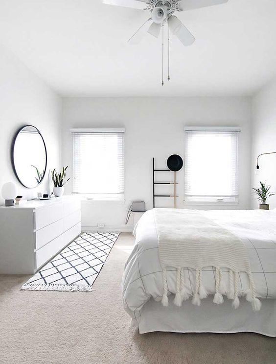una camera da letto scandinava ariosa con molti tessuti bianchi, a righe e nappe, uno specchio con cornice nera, una credenza