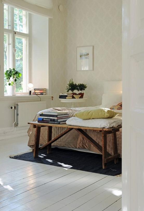 un'accogliente camera da letto scandinava con carta da parati stampata, un pavimento in legno bianco, un letto bianco e una panca di legno grezzo ai piedi