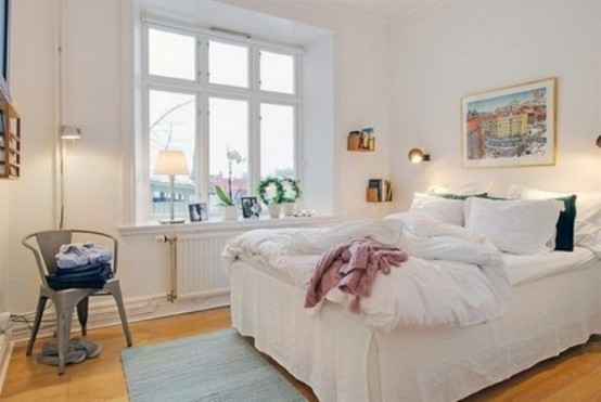 un'accogliente camera da letto scandinava con un letto bianco, una sedia in metallo, un tappeto e un'opera d'arte