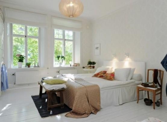 una camera da letto scandinava ariosa con tutto ciò che è bianco, una lampada a sospensione e tessuti colorati