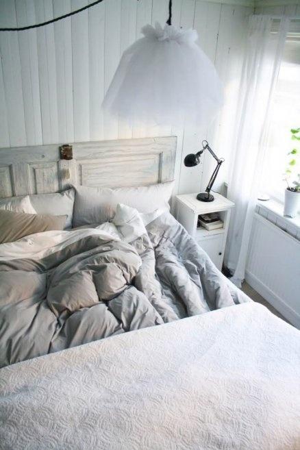 una camera da letto scandinava piena d'aria con pareti bianche, un letto in legno imbiancato, comodini bianchi e lampade a sospensione