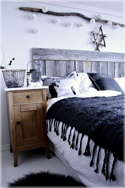 una camera da letto nordica con un letto in legno stagionato, un comodino in legno rustico, luci sopra il letto e cestini