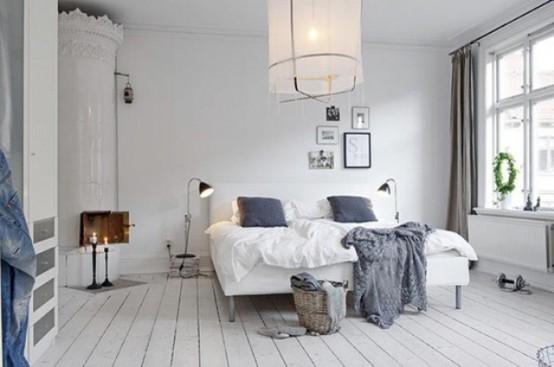 una camera da letto scandinava ariosa con una stufa bianca, un letto imbottito, una lampada a sospensione, mobili contenitori e lampade