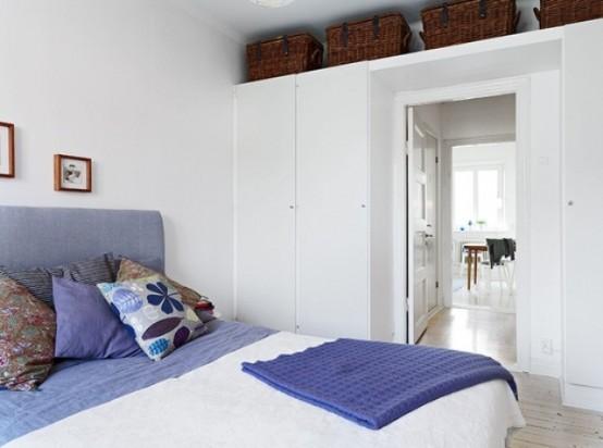 una camera da letto scandinava ariosa in bianco, con tocchi viola, eleganti contenitori e cesti per la conservazione