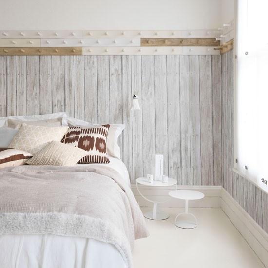 una camera da letto scandinava ariosa con legno imbiancato alle pareti, un letto comodo, comodini e ganci sul muro