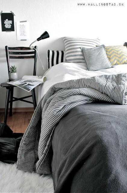 una camera da letto nordica chic con un letto nero, biancheria da letto a righe, una sedia nera, una lampada accattivante