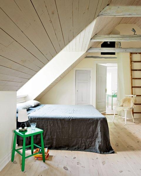 una laconica camera da letto nordica mansardata con lucernario, pareti e pavimento rivestiti in legno, alcuni mobili vintage