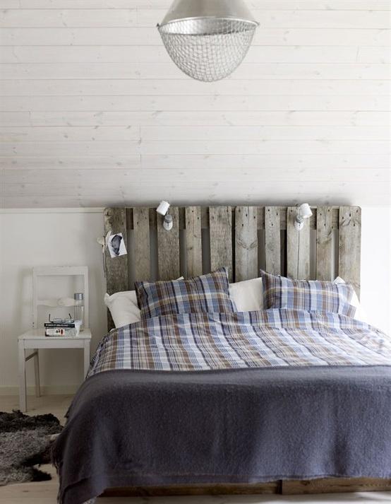 una camera da letto nordica rustica con un soffitto a battente, un letto in legno stagionato, una sedia bianca e una lampada a sospensione