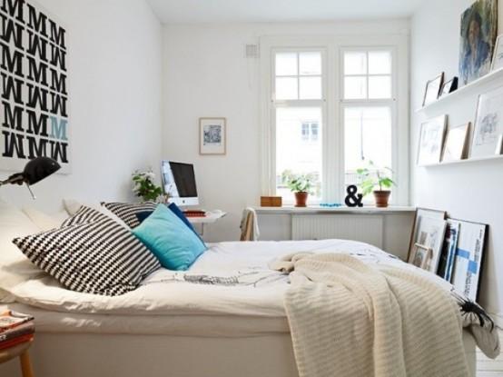 una piccola camera da letto scandinava con un letto bianco, scaffali aperti per riporre oggetti, una scrivania nell'angolo e alcuni elementi grafici