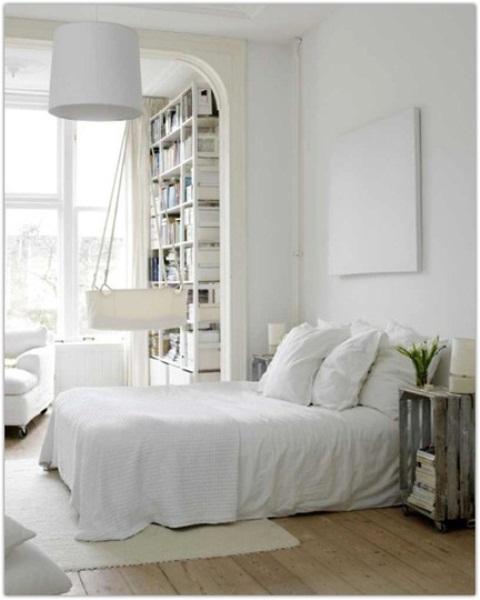 una camera da letto nordica ariosa con mobili e biancheria da letto bianchi, un'opera d'arte, una lampada a sospensione e una culla appesa accanto al letto