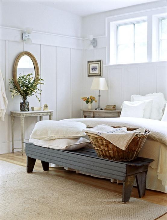 una camera da letto rustica incontra quella nordica con una panca scura, mobili vintage, uno specchio, un comodino imbiancato e una lampada