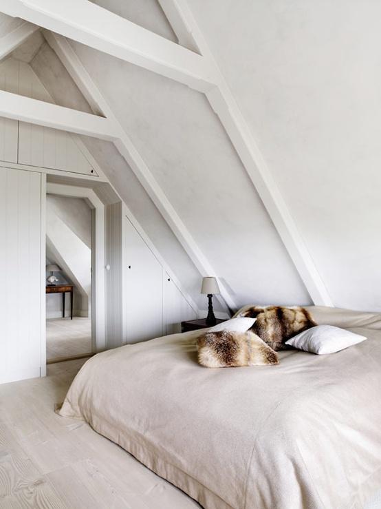 una piccola camera da letto nordica neutra a mansarda con un letto neutro e un comodino scuro