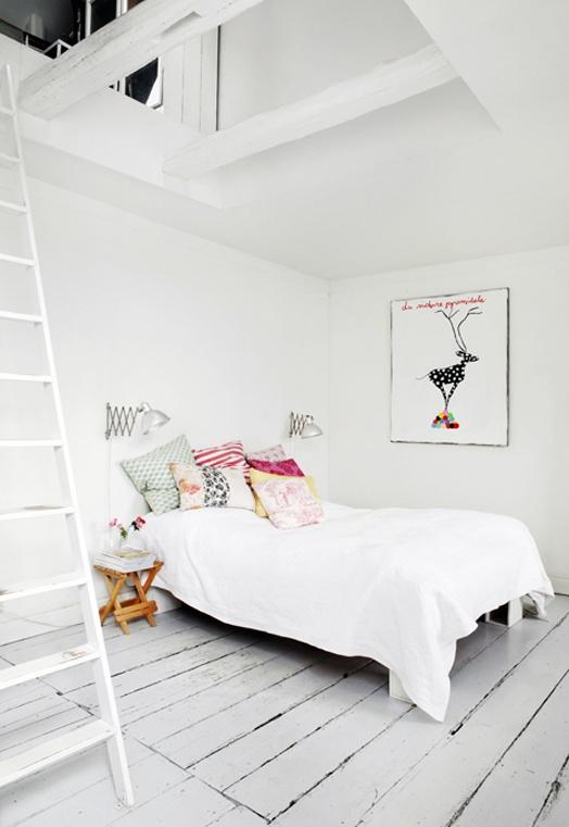 una camera da letto scandinava ariosa con solo un letto, una sedia pieghevole e un'opera d'arte più pavimento in legno imbiancato