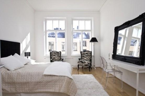 una camera da letto scandinava ariosa con un letto blakc, specchio, sedie con una stampa zebrata e una lampada da terra