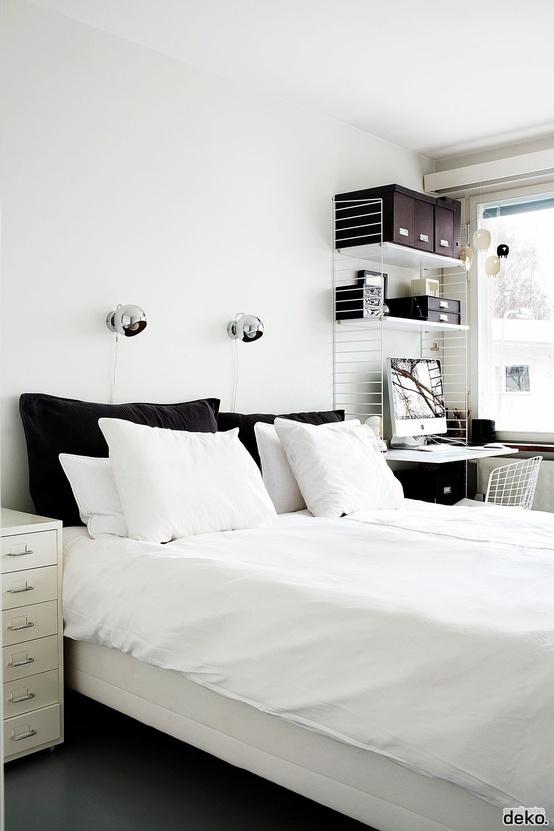 una laconica camera da letto nordica con mobili in legno neutro, un accogliente spazio di lavoro nell'angolo, una sedia in filo metallico e lampade da parete