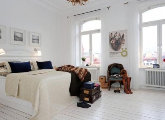 una camera da letto neutra con un letto bianco, opere d'arte, cassapanche scure per la conservazione e altri dettagli per più drammaticità