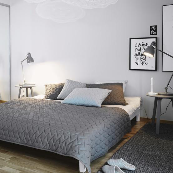 un'elegante camera da letto color talpa con un letto bianco, sgabelli in legno al posto dei comodini, lampade e opere d'arte grafiche