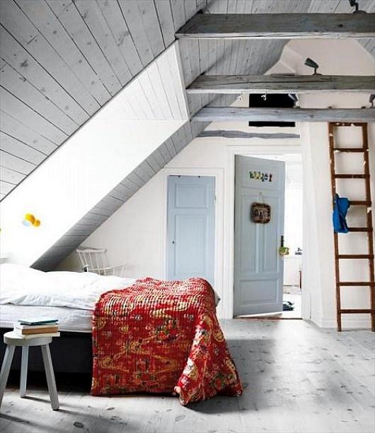una camera da letto nordica mansardata con assi di legno sul soffitto, un lucernario, mobili vintage e una scala
