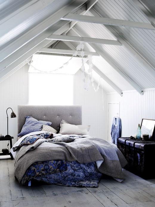 una camera da letto nordica piena di luce con assi e travi bianche sul soffitto, un letto con rivestimento grigio e biancheria da letto luminosa